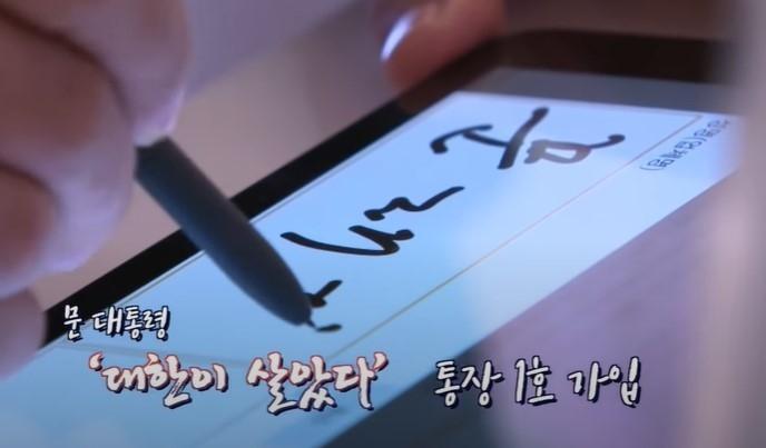 문재인 대통령이 KB국민은행 '대한이 살았다' 통장1호 가입자로 서명하는 모습[이미지=KTV 캡처]